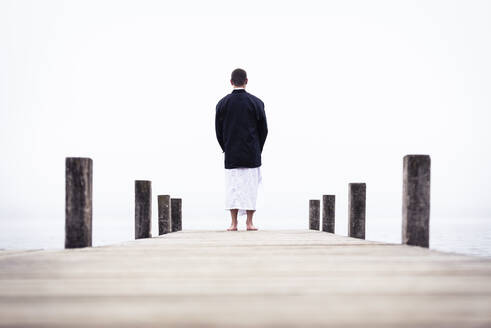Back view of barefoot man meditating on jetty at Lake Starnberg, Germany - WFF00095