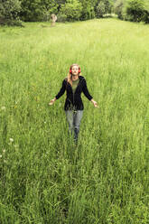Young woman with red headphones meditating on a meadow, Baitoni, Italy - WFF00098