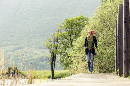 Young woman with red headphones walking on boardwalk at Lake Idro, Baitoni, Italy - WFF00101