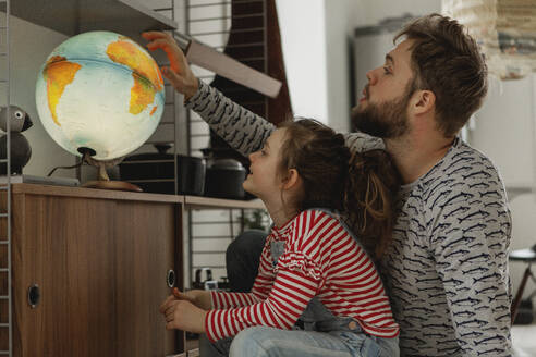 Girl with father looking at globe - JOHF01996
