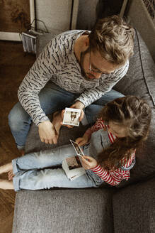 Father and daughter looking at pictures - JOHF02002