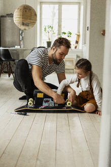 Father and daughter checking skateboard wheels - JOHF02017