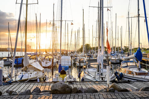 Germany, Schleswig-Holstein, Niendorf, Various boats moored in harbor at sunset - EGBF00322