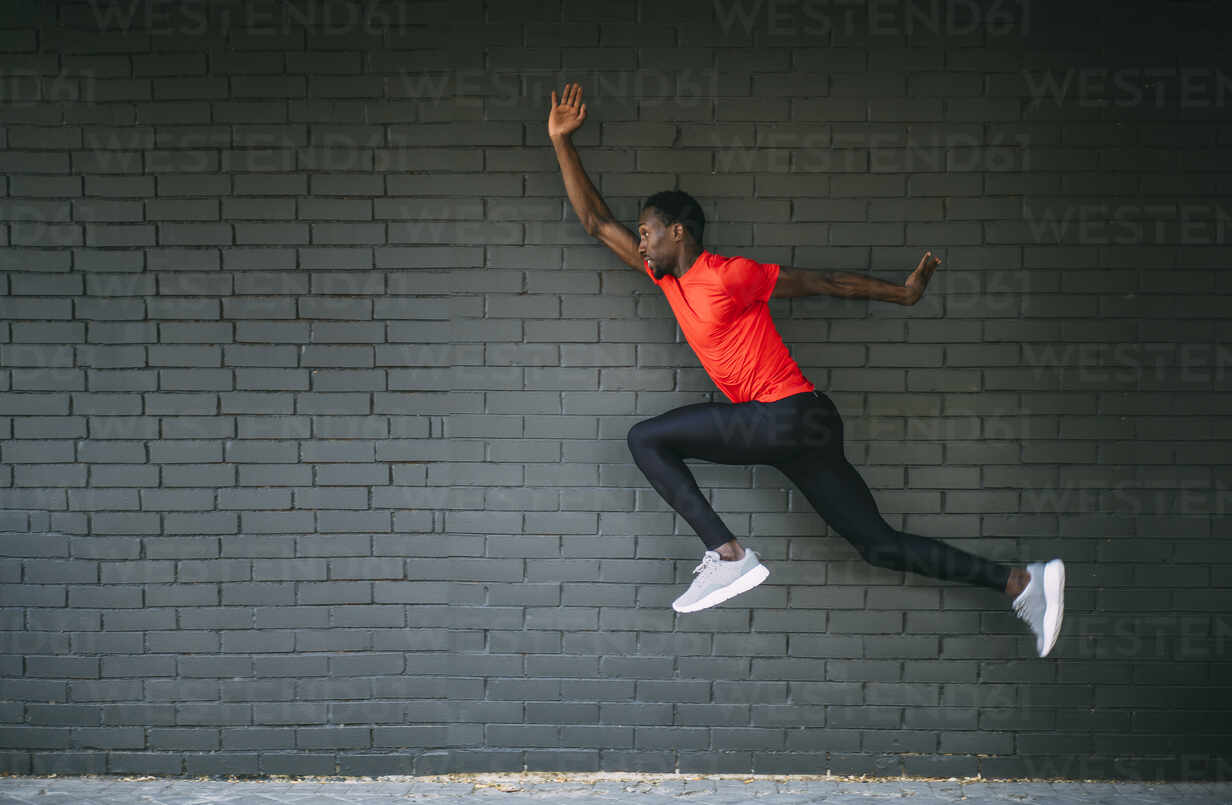 Young sportive man jumping in front of a brick wall - OCMF00760 - Oscar Carrascosa Martinez/Westend61
