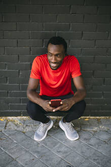Smiling young sportive man crouching in front of a brick wall using his smartphone - OCMF00769