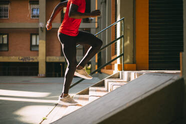 Young sportive man running upstairs on outdoor staircase - OCMF00775