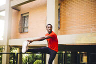 Young sportive man doing stretching exercise outdoors - OCMF00778