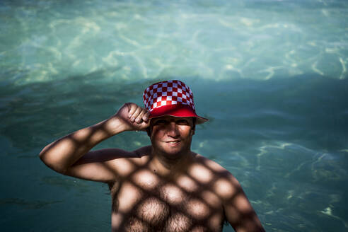 Portrait of overweight man with hat in pool in shady area - OCMF00779