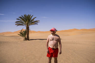 Overweight man with swimming shorts and hat standing in the desert of Morocco - OCMF00782