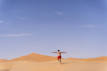 Overweight man with swimming shorts running in the desert of Morocco - OCMF00785