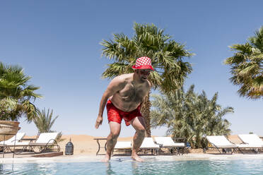 Overweight man jumping into swimming pool - OCMF00791