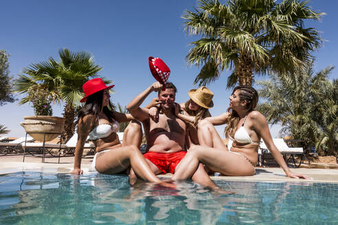 Overweight man surrounded by affectionate beautiful women at the poolside - OCMF00797