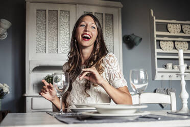 Portrait of laughing young woman sitting at laid table in country style kitchen - WFF00105