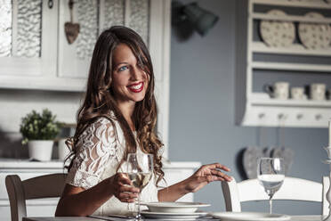 Portrait of smiling young woman sitting at laid table in country style kitchen - WFF00108