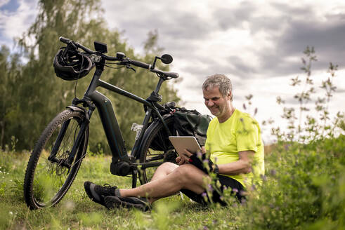 Mature man using digital tablet during his bike tour with an e-bike - BFRF02094