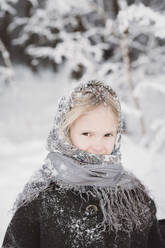 Portrait of snow-covered little girl in winter forest - EYAF00494