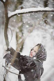 Portrait of smiling little girl shaking tree in winter forest - EYAF00500