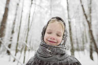 Portrait of happy little girl wearing headscarf in winter forest - EYAF00503