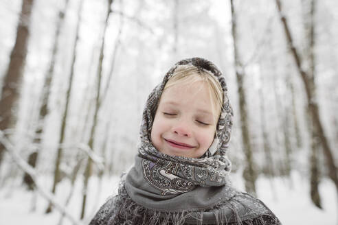 Portrait of happy little girl wearing headscarf in winter forest - EYAF00503