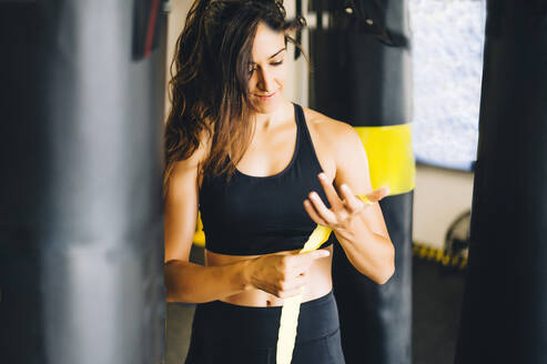 Female boxer bandaging her hands in a gym - CJMF00029