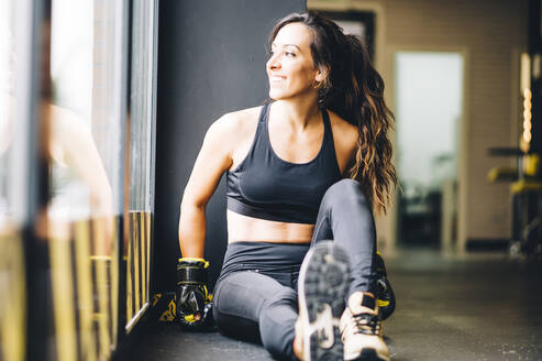 Smiling female boxer resting after boxing training - CJMF00032