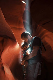 Father kissing his daughter in a baby carrier,  Antelope Canyon, Page, Arizona, United States - GEMF03193