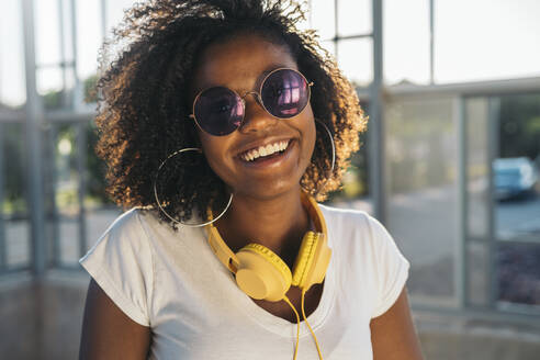 Portrait of happy young woman with headphones and sunglasses - MPPF00074