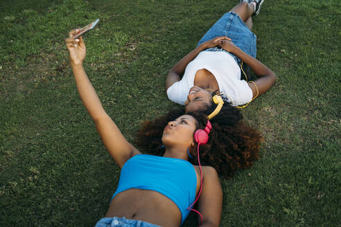 Two young women with headphones lying on a meadow taking selfie with smartphone - MPPF00086