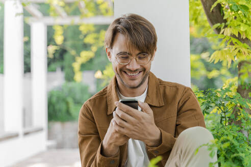 Portrait of laughing man looking at cell phone - AFVF04042