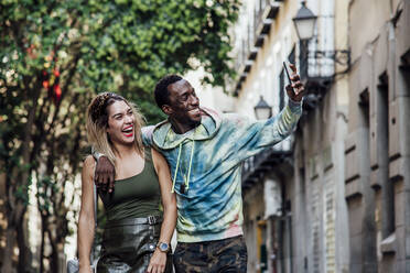 Portrait of laughing couple taking selfie with smartphone, Madrid, Spain - CJMF00045