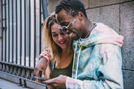 Smiling couple using cell phone outdoors - CJMF00048