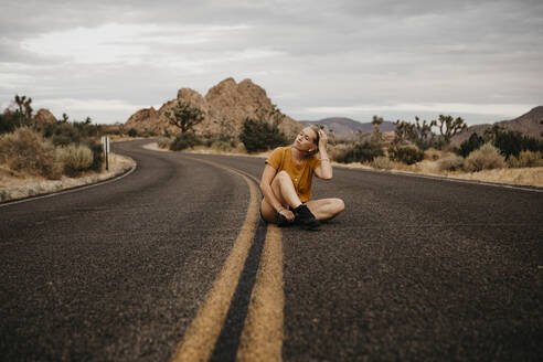 Woman sitting on road, Joshua Tree National Park, California, USA - LHPF01010