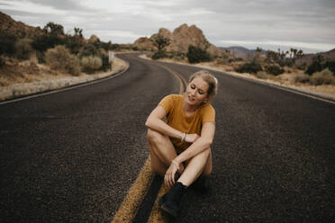 Woman sitting on road, Joshua Tree National Park, California, USA - LHPF01013