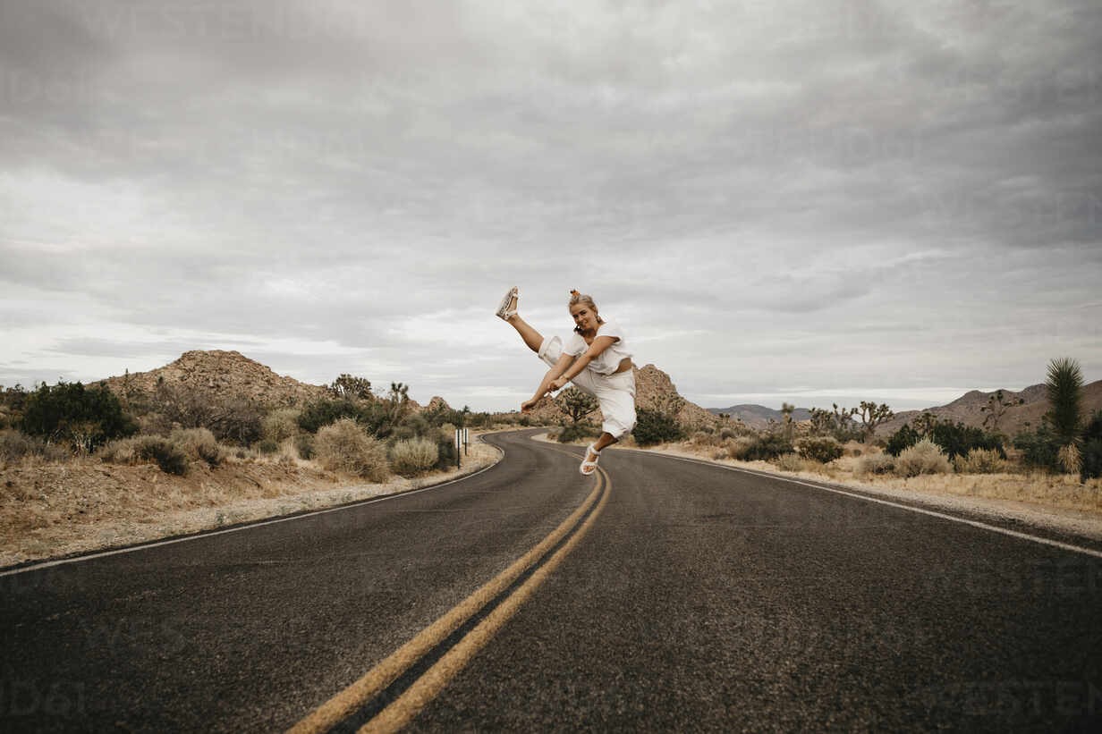 Woman jumping on road, Joshua Tree National Park, California, USA - LHPF01016 - letizia haessig photography/Westend61