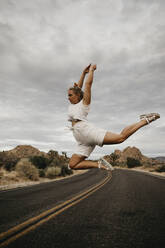 Woman jumping on road, Joshua Tree National Park, California, USA - LHPF01019