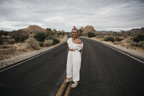 Happy woman standing on road, Joshua Tree National Park, California, USA - LHPF01022