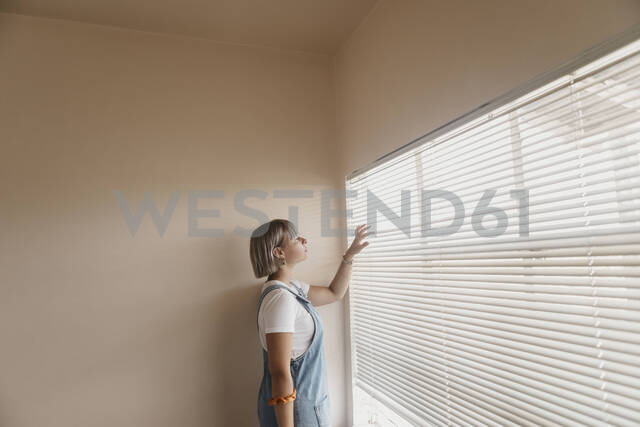 Young woman looking through blinds at the window - LHPF01034 - letizia haessig photography/Westend61