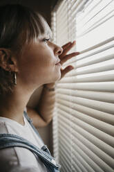 Young woman looking through blinds at the window - LHPF01037