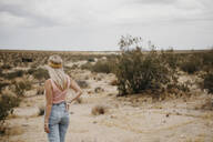 Young woman standing in desert landscape, Joshua Tree National Park, California, USA - LHPF01043