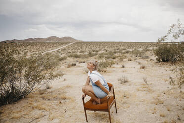Woman crouching on a chair in desert landscape, Joshua Tree National Park, California, USA - LHPF01049