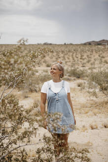 Young woman standing in desert landscape, Joshua Tree National Park, California, USA - LHPF01055