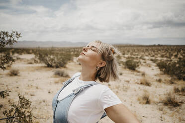 Young woman in desert landscape with closed eyes, Joshua Tree National Park, California, USA - LHPF01058