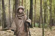 Portrait of boy wearing brown rain coat standing in autumnal forest - EYAF00511