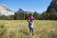 Back view of father carrying little daughter on his shoulders, Yosemite National Park, California, USA - GEMF03196