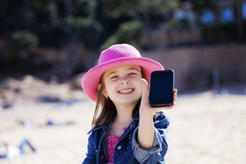 Portrait of grinning little girl showing her mobile phone on the beach - XCF00277