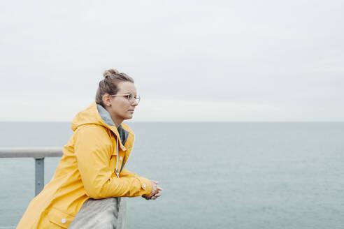 Young woman wearing yellow rain coat - NAF00120