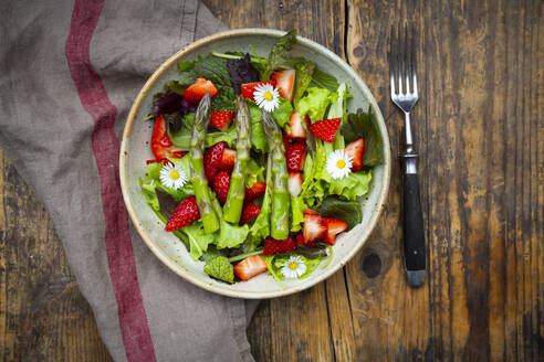 Close-up of salad with green asparagus, strawberries and daisies - LVF08316