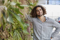 Portrait of smiling young man in front of plant wall - SUF00605