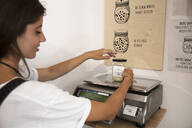 Young woman in packaging-free supermarket weighing goods on scale - SUF00617