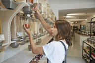Young woman shopping in packaging-free supermarket - SUF00623